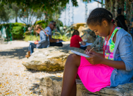 A girl sketches outdoors during Junior Docent Art Camp