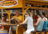 People drinking and peddling The Pedal Pub