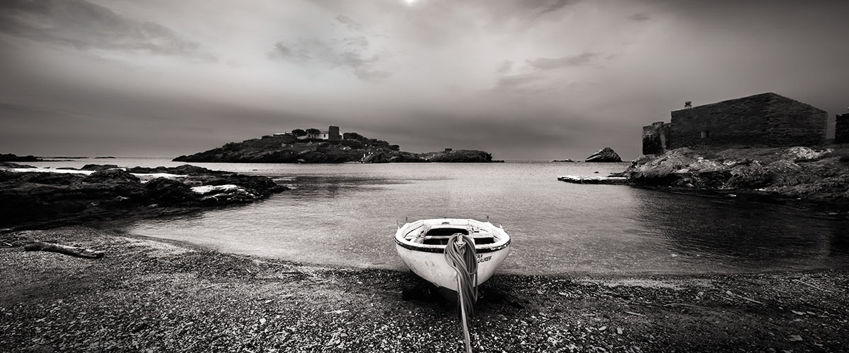 Visions of Dalí's Spain: Photograph of a boat on the shore of a seascape