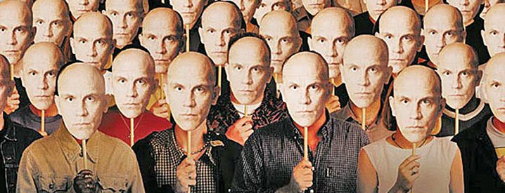 People holding masks of John Malkovich's face
