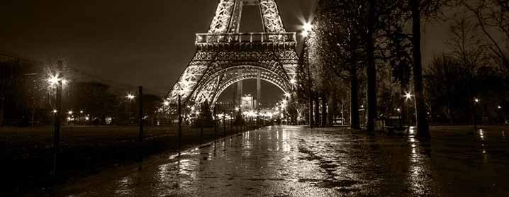 Black and white photo of Paris street at night and Eiffel Tower