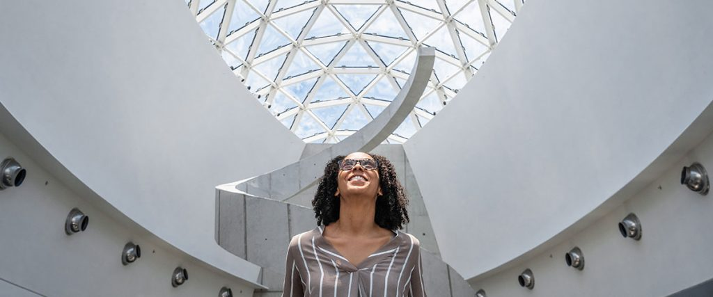Woman stands in front of The Dali's helical staircase
