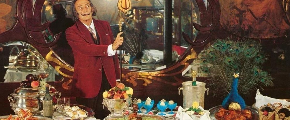 Salvador Dalí standing next to party dinner table with food