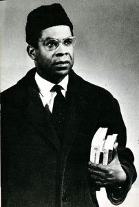 Portrait of Aime Cesaire with books and hat.