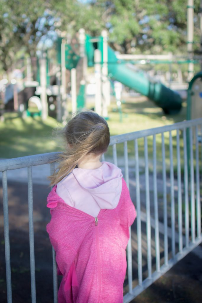 Child gazes at park from overlook